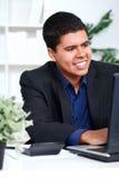 Executivo de sorriso do homem de negócio que usa um computador fotos de stock royalty free