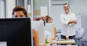 Executivo de sorriso que está com os braços cruzados quando colegas que falam nos auriculares 4k vídeos de arquivo