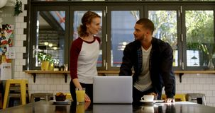 Executivo do homem e de mulher que discute sobre um portátil no bar 4K 4k do escritório vídeos de arquivo