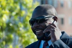 Executivo em óculos de sol desgastando do telefone de pilha Fotografia de Stock Royalty Free