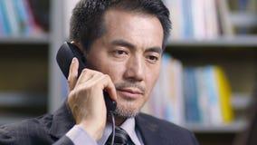 Executivo empresarial asiático que fala no telefone filme