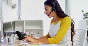 Executivo empresarial com auriculares usando computadores na mesa no escritório 4k vídeos de arquivo