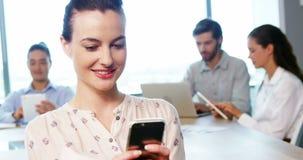 Executivo empresarial fêmea que usa o telefone celular vídeos de arquivo
