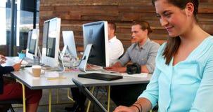 Executivo empresarial fêmea que usa a tabuleta digital quando colega que trabalha na mesa vídeos de arquivo