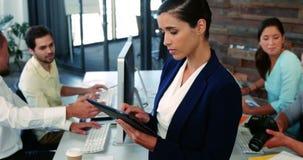 Executivo empresarial fêmea que usa a tabuleta digital quando colega que trabalha na mesa video estoque