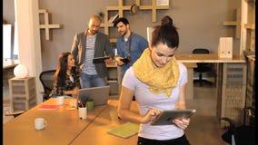 Executivo empresarial fêmea que usa a tabuleta digital quando seu colega de trabalho que interage no fundo filme