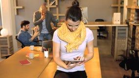 Executivo empresarial fêmea que usa a tabuleta digital quando seu colega de trabalho que interage no fundo vídeos de arquivo