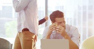 Executivo empresarial masculino enrijecido que usa o portátil filme