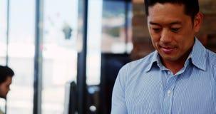Executivo empresarial masculino que usa a tabuleta digital video estoque