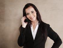 Executivo empresarial novo que sorri quando no telefone Fotografia de Stock