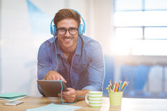 Executivo empresarial que escuta a música na tabuleta digital Foto de Stock Royalty Free