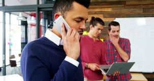 Executivo empresarial que fala no telefone celular quando colega que trabalha no fundo filme
