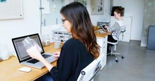 Executivo empresarial que usa o portátil ao guardar o frasco dos seixos video estoque