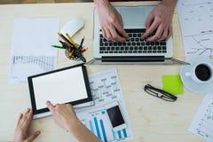 Executivo empresarial que usa o portátil e a tabuleta digital em sua mesa Imagens de Stock