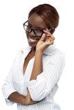 Executivo fêmea africano que ajusta seu espetáculo imagem de stock
