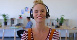 Executivo fêmea caucasiano bonito nos auriculares que sentam-se na mesa 4k filme