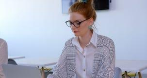 Executivo fêmea caucasiano bonito que usa o portátil no escritório moderno 4k video estoque