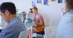 Executivo fêmea caucasiano novo que trabalha na mesa no escritório moderno 4k vídeos de arquivo
