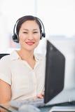 Executivo fêmea com auriculares usando o computador na mesa fotografia de stock