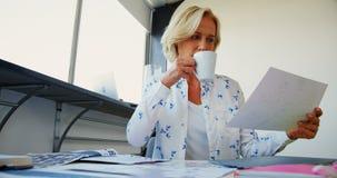 Executivo fêmea comendo o café ao trabalhar no escritório video estoque