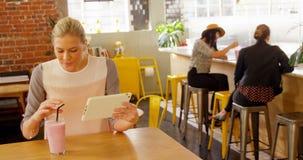Executivo fêmea comendo o milk shake ao usar a tabuleta digital 4k filme