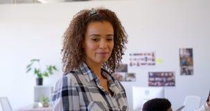 Executivo fêmea da misturado-raça bonita que usa a tabuleta digital no escritório moderno 4k video estoque