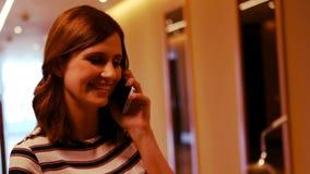 Executivo fêmea de sorriso que fala no telefone celular no corredor filme