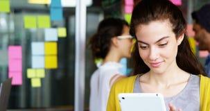 Executivo fêmea de sorriso que usa a tabuleta digital video estoque