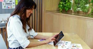 Executivo fêmea de sorriso que usa a tabuleta digital na mesa filme