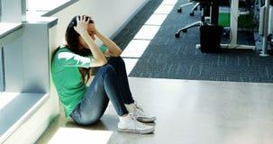 Executivo fêmea deprimido que senta-se no assoalho video estoque
