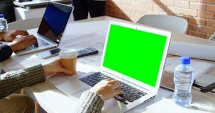 Executivo fêmea que come o café ao usar o portátil 4k filme