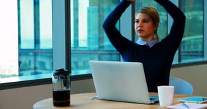 Executivo fêmea que estica suas mãos ao trabalhar no escritório video estoque