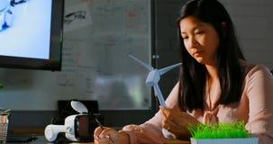 Executivo fêmea que examina um moinho de vento 4k modelo video estoque