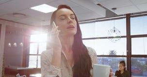 Executivo fêmea que fala no telefone celular ao comer o café 4k filme