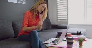 Executivo fêmea que fala no telefone celular ao usar o portátil em um escritório moderno 4k video estoque