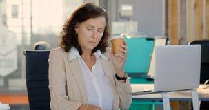 Executivo fêmea que usa o portátil e o telefone celular no escritório 4k filme