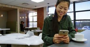 Executivo fêmea que usa o telefone celular ao comer o café 4k video estoque