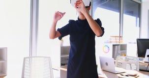 Executivo fêmea que usa os auriculares 4k da realidade virtual vídeos de arquivo