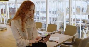 Executivo fêmea que usa a tabuleta digital no escritório 4k filme