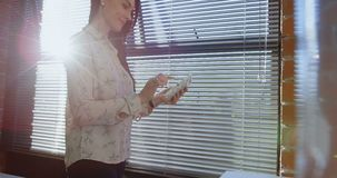 Executivo fêmea que usa a tabuleta digital perto da janela 4k filme