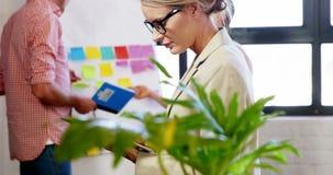 Executivo fêmea que usa a tabuleta digital quando colegas que discutem na placa branca vídeos de arquivo