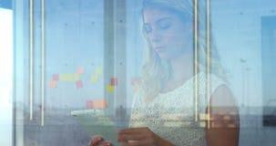 Executivo fêmea que usa uma tabuleta na frente das notas pegajosas 4K 4k filme