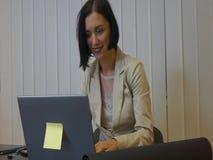 Executivo fêmea sério que trabalha em sua mesa com portátil filme