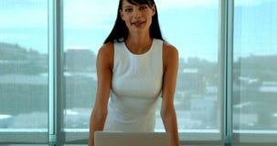 Executivo fêmea seguro em sua mesa no escritório video estoque