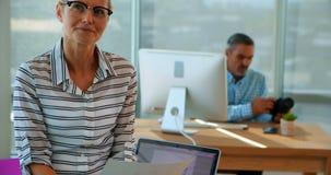 Executivo fêmea seguro que senta-se em sua mesa video estoque
