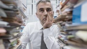 Executivo frustrante sobrecarregado com o documento imagens de stock