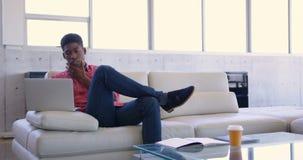 Executivo masculino afro-americano consider?vel que usa o port?til no escrit?rio moderno 4k vídeos de arquivo