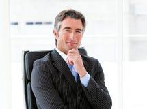 Executivo masculino ambicioso que senta-se em seu escritório imagem de stock royalty free