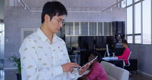 Executivo masculino asi?tico que usa a tabuleta digital no escrit?rio moderno 4k vídeos de arquivo