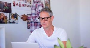Executivo masculino caucasiano maduro que usa o portátil no escritório moderno 4k vídeos de arquivo
